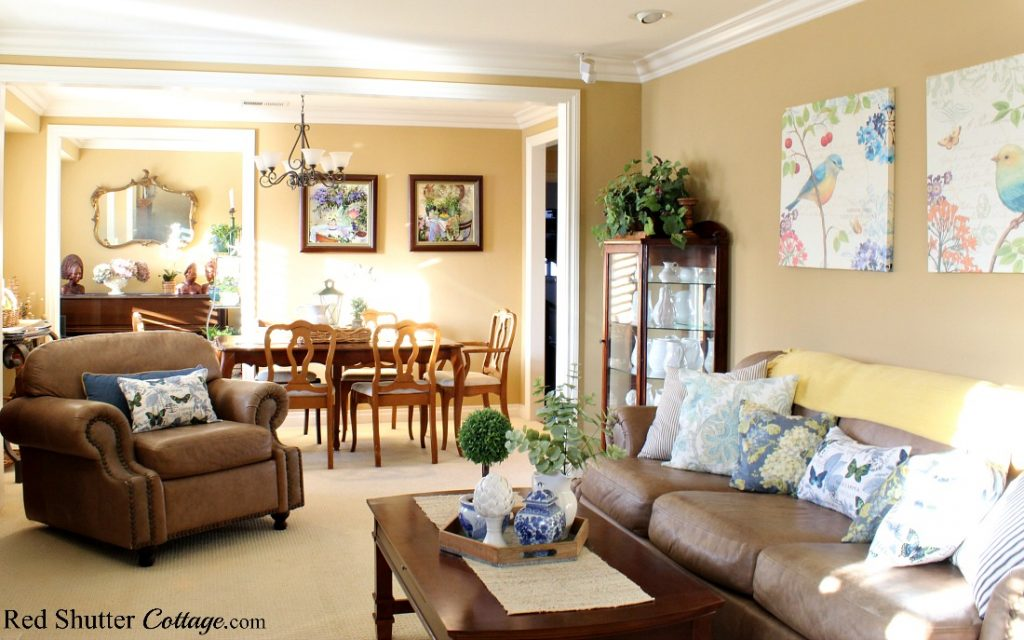 A collage pattern appears on both the wall hangings and the butterfly pillows in this springtime living room. www.redshuttercottage.com