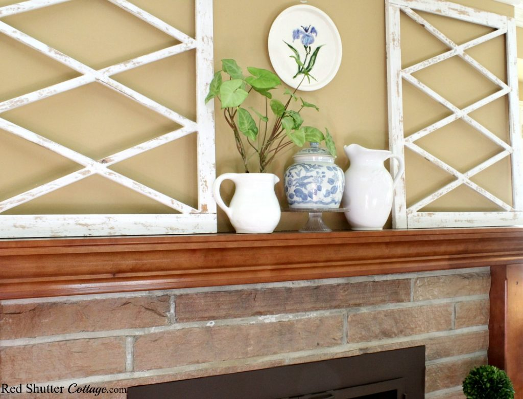 A plate with a blue iris is part of this mantel in my springtime living room. www.redshuttercottage.com