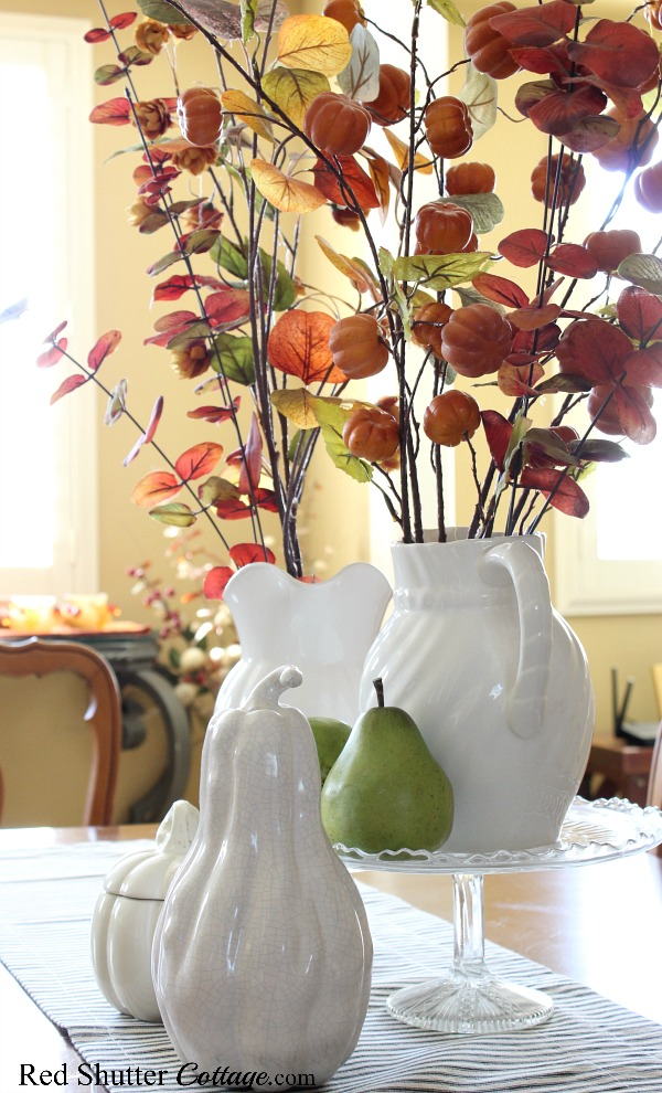 A fall vingette on the dining table with autumn-colored branches and white pitchers. www.redshuttercottage.com