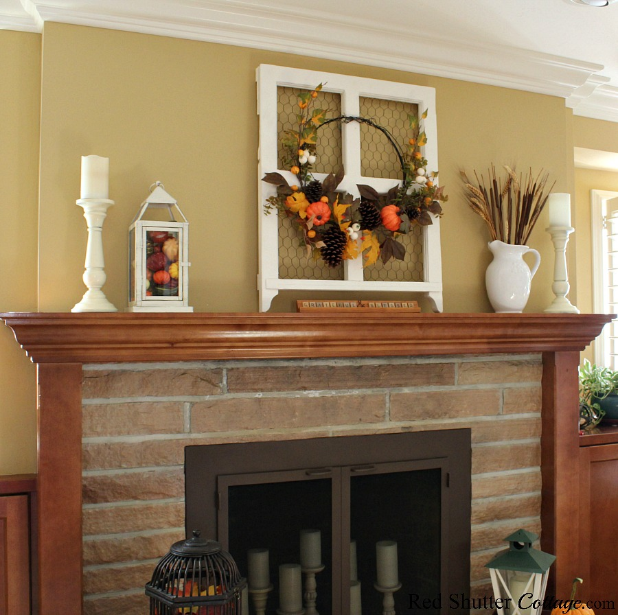 A fall fireplace and mantel, complete with a wreath decorating a window frame, and a white pitcher of wheat. www.redshuttercottage.com