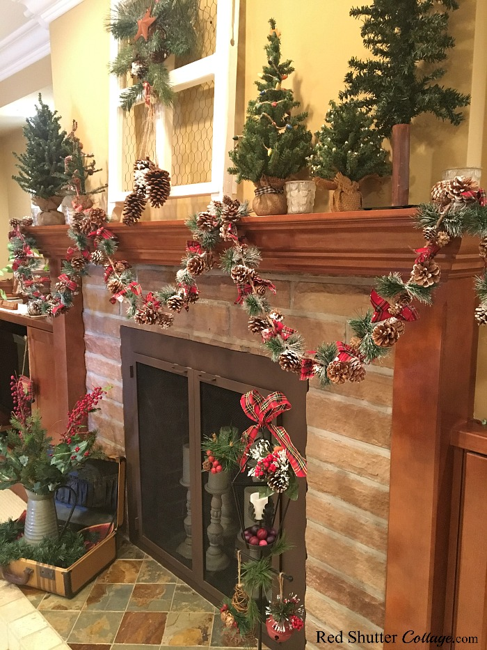 Pine cones, plaid and greenery decorate this Christmas 2018 mantel. www.redshuttercottage.com