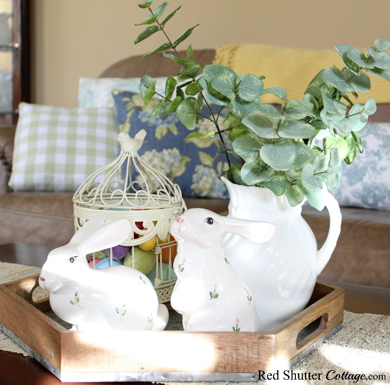 A pair of ceramic bunnies, a bird cage and a white pitcher create a fresh Easter coffee table vignette. www.redshuttercottage.com